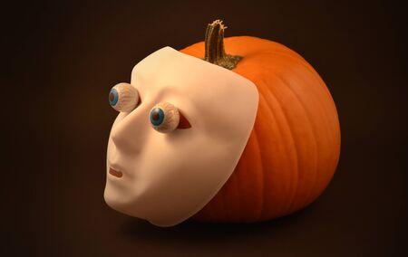 Halloween pumpkin. Halloween pumpkin with eyes and scary mask. Creepy halloween pumpkin on a dark background. Plastic human mask on pumpkin. Halloween white face mask