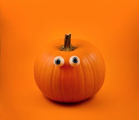 Halloween pumpkin. Halloween pumpkin. Cute halloween pumpkin with chocolate eyes. Single pumpkin isolated on orange background