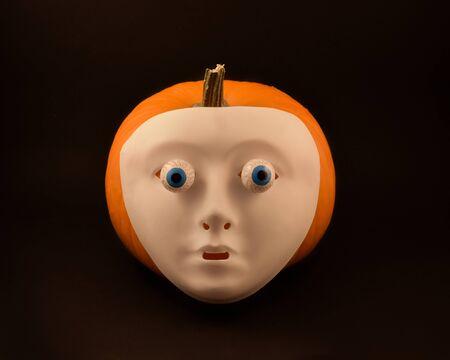 Halloween pumpkin. Halloween pumpkin with eyes and scary mask. Creepy halloween pumpkin on black background. Plastic human mask on pumpkin. Halloween white face mask