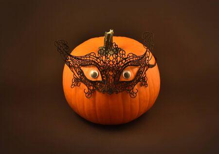 Halloween pumpkin stock photography. Halloween pumpkin on a dark background. Black lace mask on pumpkin. Halloween pumpkin Фото со стока