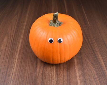 Halloween pumpkin. Halloween pumpkin with eyes on a wooden background. Single halloween pumpkin on a dark background