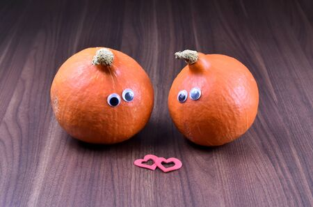 Couple in love stock photography Halloween pumpkin in love. Halloween pumpkins on wooden background. Love pumpkin stock images. Cute halloween pumpkin with eyes. Enamored pumpkin with heart