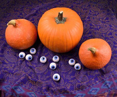 Halloween pumpkin. Three halloween pumpkins with chocolate eyes. Creepy halloween pumpkin. Autumn pumpkin with drapery. Autumn still life with pumpkin.   Фото со стока
