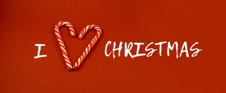I love Christmas sign illustration. Candy Cane Heart Shape. Sweet Christmas symbol. Christmas banner. Candy stick on red background. Christmas Candy Cane images Фото со стока - 132369491