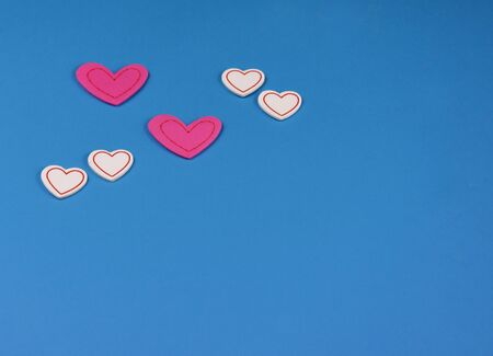 Pink hearts on blue background stock images. Valentines Day background. Hearts on blue background with copy space for text. Valentines Day concept. White and pink hearts shape