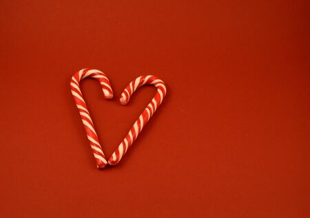 Candy Cane Heart shape stock images. Sweet Christmas symbol. Candy stick on red background. Christmas candy cane stock images. Candy cane on red background with copy space for text