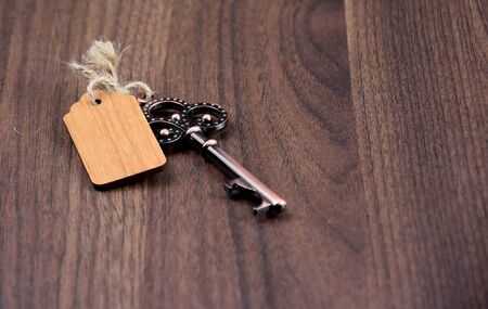 Decorative metal key stock images. Decorated key isolated on a wooden background. Romantic key with wooden label. Vintage key on the table