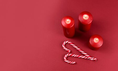 Red christmas candles with candy cane stock images. Christmas candy cane stock images. Red christmas candles on red background with copy space for text. Christmas still life concept