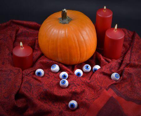 Halloween pumpkin. Halloween pumpkin with chocolate eyes. Halloween pumpkin on red background. Pumpkin with red drapery. Pumpkin on a fabric background. Halloween pumpkin with red candles. Halloween decoration still life