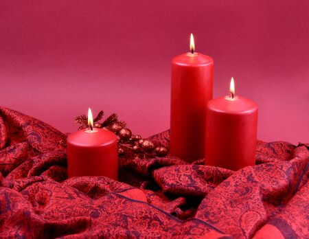 Red Christmas Candles stock images. Red Christmas candles on a red background. Christmas still life concept. Red Christmas decoration. Christmas candles with red drapery