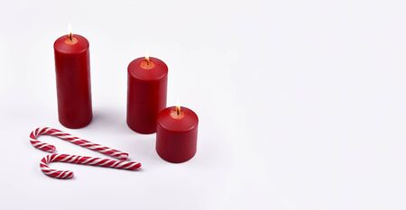 Red christmas candles with candy cane stock images. Christmas candy cane stock images. Red christmas candles on white background with copy space for text. Christmas still life concept Zdjęcie Seryjne
