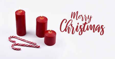 Merry Christmas sign stock images. White Christmas background with candles and candy cane. Christmas still life concept. Christmas candy cane stock images