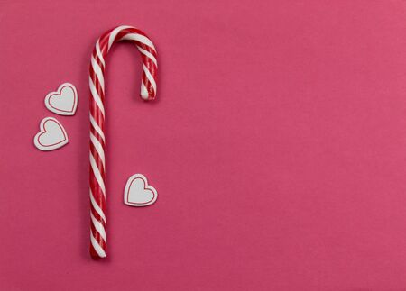 Candy Cane with hearts on pink background stock images. Candy stick on a pink background. Christmas candy cane stock images. Candy Cane on Red Background with Copy Space for Text. Sweet Christmas