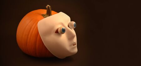 Halloween pumpkin with eyes. Halloween pumpkin with eyes and scary mask. Creepy halloween pumpkin photo. Plastic human mask on pumpkin. Halloween white face mask