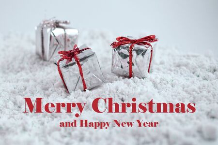 Merry Christmas and Happy New Year images. Happy New Year Inscription on snowy background. Merry Christmas sign on snowy background with gift boxes. Winter christmas background Фото со стока - 132432462