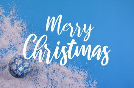 Merry Christmas sign on blue background. Merry Christmas inscription on snowy background. Merry Christmas Sign on Snowy Background with Blue Ball. Winter christmas background Фото со стока