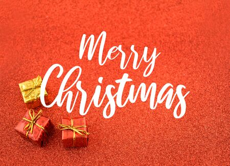 Merry Christmas Sign. Red Holiday Background with Presents. Christmas gift box. Red decorations on shiny background. Merry Christmas Sign