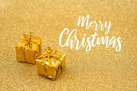 Merry Christmas Sign. Stock photography Golden Christmas background. Golden Holiday Background with Presents. Christmas gift boxes. Golden decorations on shiny background Фото со стока - 132487810