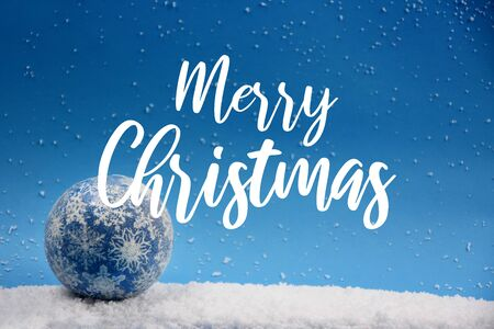 Merry Christmas sign on blue background. Merry Christmas inscription on snowy background. Merry Christmas Sign on Snowy Background with Blue Ball. Winter christmas background Фото со стока - 132487811