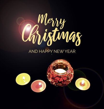 Merry Christmas and Happy New Year sign with candles on a dark background. Christmas candles on black background. Christmas light decoration background. Christmas greeting card