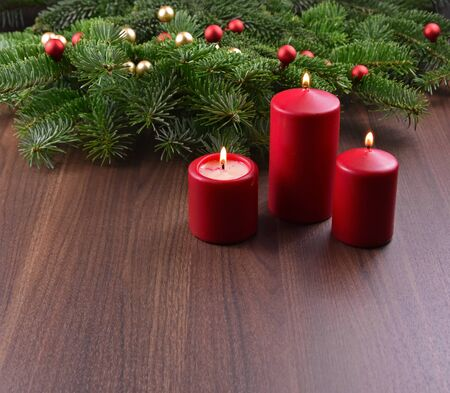 Red candles on christmas background stock images. Christmas ornament. Red Christmas candles on the table. Christmas background with copy space for text Фото со стока - 135075593
