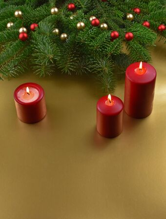 Red candles on christmas background stock images. Christmas ornament. Red Christmas candles on a golden background. Christmas background with copy space for text Фото со стока - 135079022