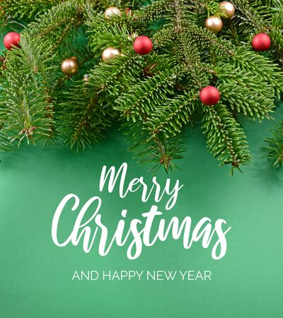 Merry Christmas and Happy New Year Sign. Christmas green background with ornate spruce branch stock images. Elegant holiday background. Christmas greeting card Фото со стока - 135098103