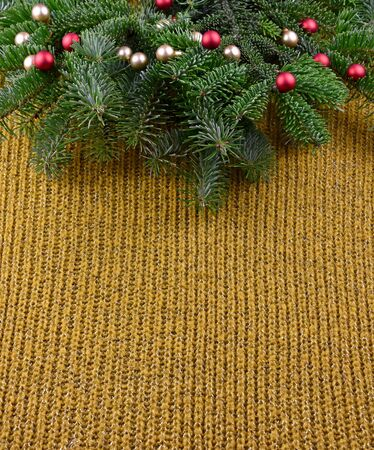 Christmas knitted background stock photography. Christmas yellow background with spruce branch stock images. Christmas tree branch. Beautiful knitted warm Christmas background Фото со стока - 135100642