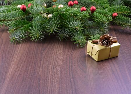 Christmas gift on wooden background stock images. Beautiful Christmas background. Christmas decorations on wooden background. Christmas tree branch with gift box. Natural Christmas images