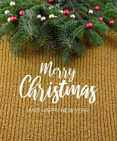 Merry Christmas and Happy New Year. Christmas Yellow Background with Ornate Spruce Branch. Christmas tree branch. Beautiful knitted warm background Фото со стока