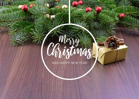 Merry Christmas and Happy New Year Sign. Christmas background with ornate spruce branch. Elegant holiday background. Christmas greeting card with gift box and spruce tree Фото со стока