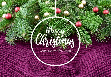 Merry Christmas and Happy New Year. Christmas purple background with ornate spruce branch. Christmas tree branch on purple background. Beautiful knitted warm background