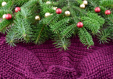 Christmas knitted background stock photography. Christmas purple background with ornate spruce branch stock images. Christmas tree branch on purple background. Beautiful knitted warm Christmas background Фото со стока