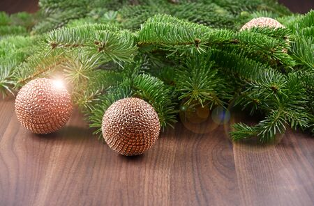 Christmas decoration with spruce branches stock photography. Christmas balls on wooden background. Golden Christmas baubles images. Shiny christmas background Фото со стока