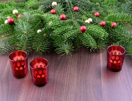 Red glass Christmas candle holders stock images. Christmas ornament. Red Christmas candlestick on a table. Beautiful Christmas Background with Spruce Branch. Фото со стока