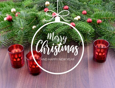 Merry Christmas and Happy New Year. Christmas background with ornate spruce branch. Christmas greeting card. Red Christmas candlestick on a table