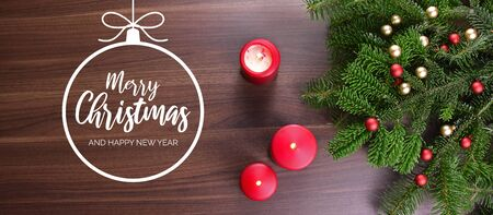 Merry Christmas and Happy New Year greeting card. Christmas background with ornate spruce branch. Christmas greeting card. Red Christmas candles on the table Фото со стока