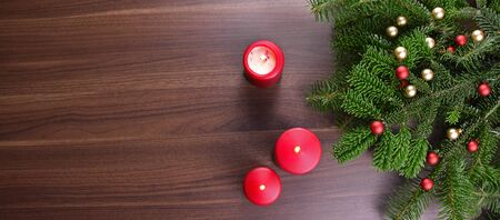 Wooden Christmas banner with tree branches and red candles. Christmas decorations on wooden background. Christmas background with copy space for text Фото со стока