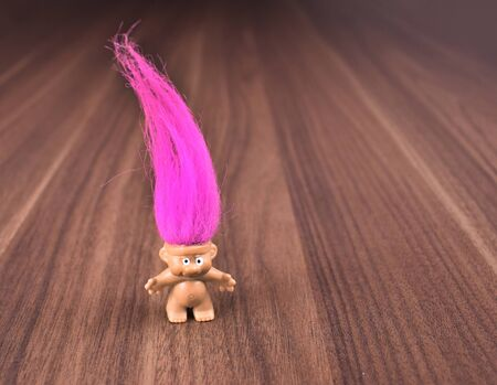 Troll figure stock images. Elf on a wooden background. Troll with pink hair. Troll girl figure. Troll toy images