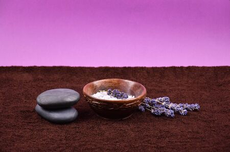 Spa and wellness setting stock images. Spa frame on purple backgound. Spa still life images. Bath salt in bowl, lava stones and lavender on brown textured background with copy space for text