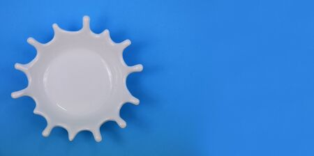 White splash stock images. White splash on blue background. White milk drop. White Bowl on Blue Background with Copy Space for Text Imagens