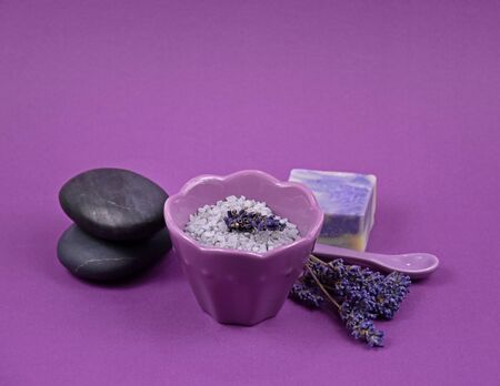 Purple spa and wellness setting. Spa frame on purple backgound. Scented spa still life. Bath salt in bowl, lava stones and lavender on purple background with copy space for text