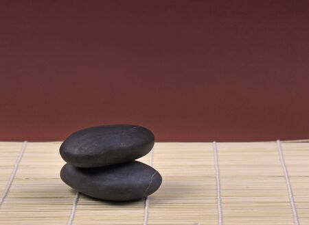 Bamboo mat stock photography Spa and wellness setting stock images. Massage stones for relaxation. Pile of black stones. Black stones on black background with copy space for text