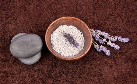 Spa setting on brown background stock images. Top view of spa setting images. Spa still life images. Bath salt in bowl, lava stones and lavender on brown textured background