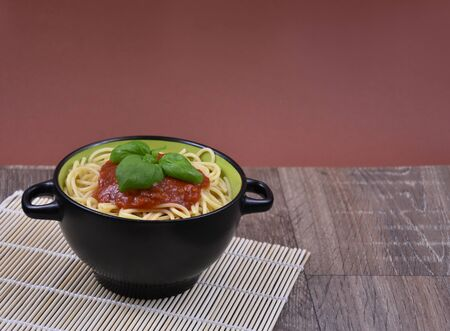 Spaghetti pasta with tomato sauce on wooden table stock images. Bowl of spaghetti. Spaghetti with basil on wooden background with copy space for text