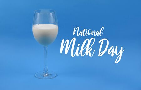 National Milk Day. Glass of milk on blue background stock images. Milk in a wine glass. Wine glass with milk on a blue background