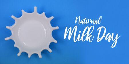 National Milk Day. White splash on blue background. White milk drop. White bowl on blue background