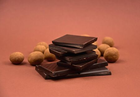 Chocolate sweets stock images. Pile of chocolate stock images. Dark chocolate on brown background. Chocolate candies isolated on white background Imagens