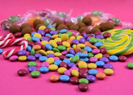 Colorful candies on pink background stock images. Sweets on pink background. Candy on a pink background. Candies  lollipops images