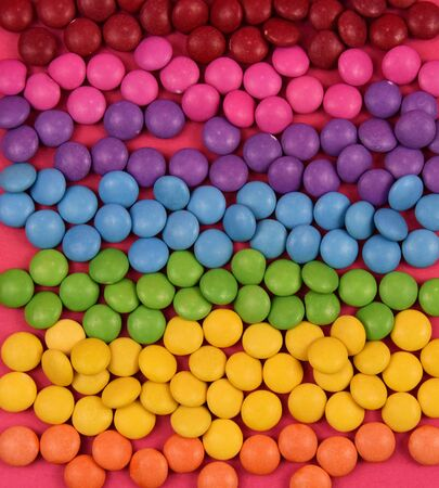 Stack of colorful candies. Colorful candies texture. Rainbow colored candy coated chocolate pieces. Mix of candies Imagens